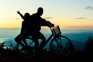 Boy with his sister riding bicycle on sunrise background.Silhoue