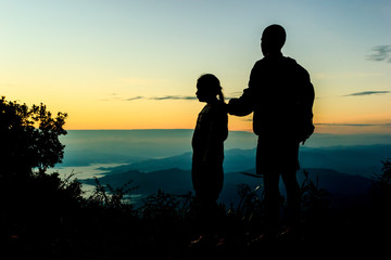 Two children, male and female standing against the sun, sunrise,