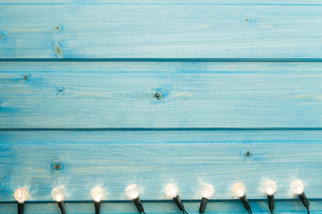 yellow Christmas lights on a blue wooden background.