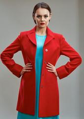 Fashion model in red coat posing in studio.