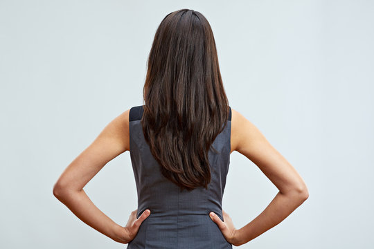 Business woman standing back with long hair. Studio isolated.