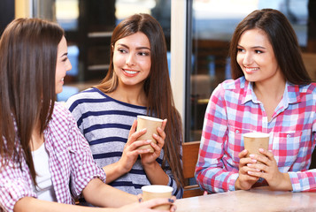 Three smiling friends speaking with coffee in hands