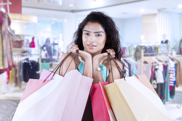 Indian woman holds shopping bags at shopping mall