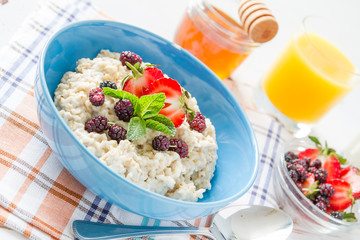 Breakfast - oatmeal with honey and berries, blue bowl
