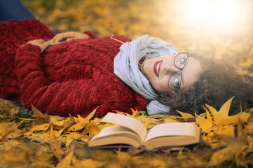 Smiling girl lying on autumn leaves in the park