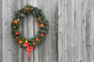 A Christmas wreath on the side of an old barn in a rural area