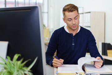 mann im büro sitzt am schreibtisch und liest in unterlagen