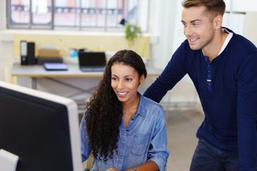 zwei gut gelaunte kollegen schauen gemeinsam auf computer