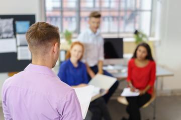 mann hält einen vortrag vor kollegen im büro
