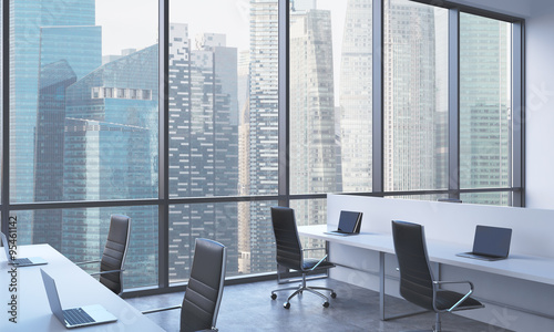 Workplaces in a bright modern open space office white tables equipped with modern laptops and
