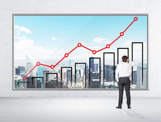 Rear view of a thoughtful businessman who looks at the New York city poster with a growing line graph and a bar chart. A wall and a floor in the room are made from concrete.