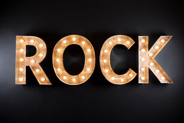 rock sign made of light bulbs over black background