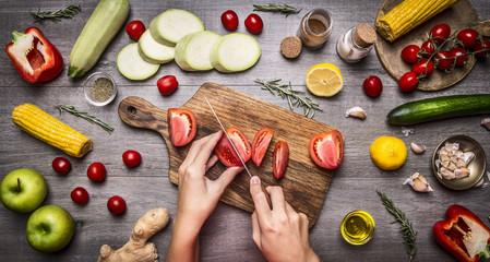 Female hand cut tomatoes on rustic grey background, around lie variety ingredients, vegetables, fruits, and spices, vegetarian food concept.