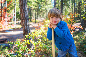 Boy leaning on a stick in forest