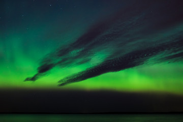 Northern lights and dark clouds over lake in finland