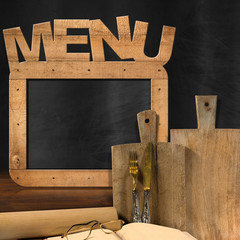 Blackboard Menu in the Kitchen / Empty blackboard with wooden frame and text Menu in the kitchen with cutting boards, silver cutlery, recipe book, eyeglasses and rolling pin. Template for food menu