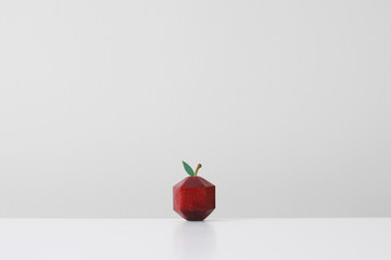 Red apple crafted into geometric shape imitating paper origami