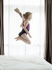 Girl in a swimming costume jumping on a bed