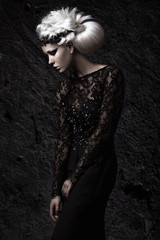 Beautiful girl in gloomy image with white wig, unusual hairstyle, black dress and dark makeup. Art beauty, fashion model