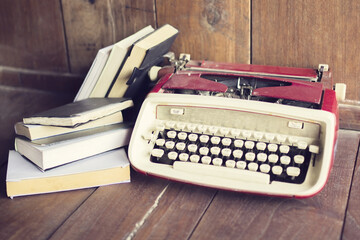 Old style typewriter with books on wooden floor