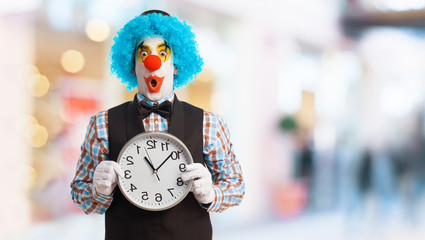 portrait of a funny clown holding a clock