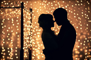 Silhouettes of lovers on a background garlands
