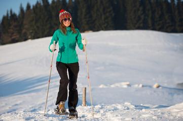 Junge Frau mit Schneeschuhen im Winter