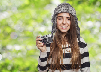 beautiful young woman taking photos in winter