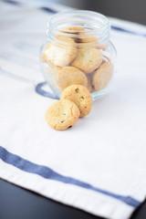 Cookies in glass jar on white napkin, kitchen