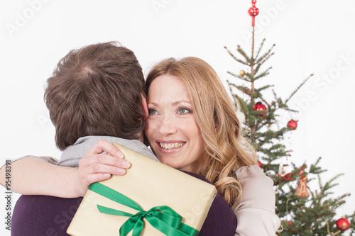 paar umarmt sich frau h lt weihnachtsgeschenk l chelnd. Black Bedroom Furniture Sets. Home Design Ideas