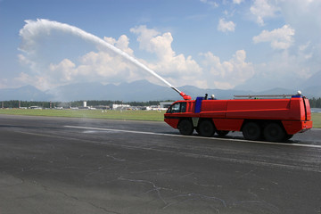 Big red Airport Firetruck using a water cannon on the runway