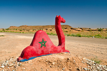 A red statue of a camel with the flag of morocco. Highway to Sahara Desert