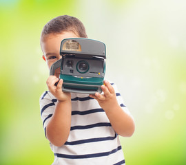portrait of a little boy taking photos with polaroid camera