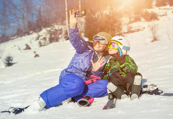Mother with son make a selfy on the snow mountain hill