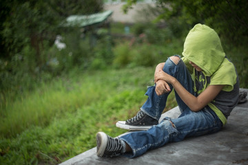 a homeless boy sits on a bench with her head bowed down
