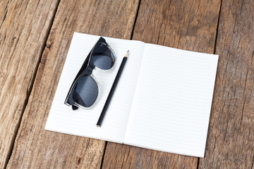 notebook sunglasses on wooden table