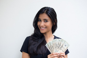 Closeup portrait, excited successful young business woman in black shirt holding money dollar bills in hand isolated white wall background. Positive emotion facial expression feeling. Financial reward