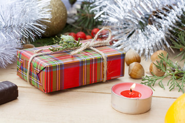 Christmas gift box and red candle with New Year's and Christmas decoration midst fruits and tinsel