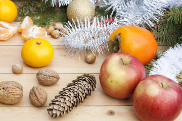 Apples in Christmas decor with Christmas tree, nuts and apples on light wooden background