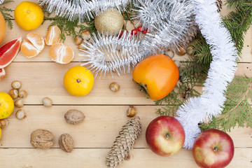 Tangerines in Christmas decor with Christmas tree, nuts and apples on light wooden background