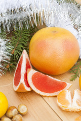 Ripe Cut Red Grapefruit with New Year's and Christmas decoration midst fruits and tinsel