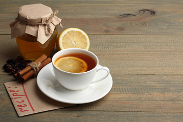 a Cup of tea with lemon and a jar of honey near a pile of drugs on wooden background