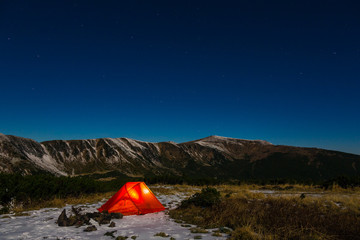 Night mountain landscape with illuminated tent. Silhouettes of snowy mountain peaks and edges night sky with many stars and milky way on background illuminated orange tent on foreground