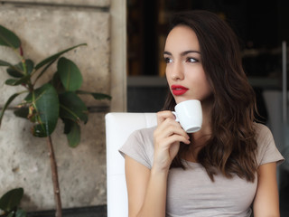 Girl sitting in cafe drinking coffee