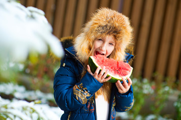 Happy toddler girl in furry winter hat outside with ripe watermelon