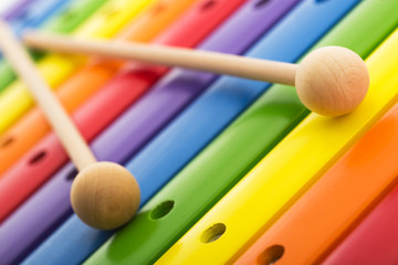 Rainbow colored wooden toy xylophone texture against white backg