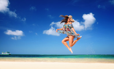 Carefree young woman is jumping into the sky