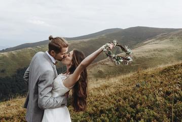 beautiful stylish groom holding fabulous happy emotional bride a