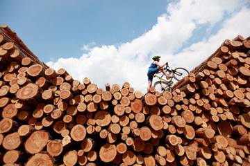 off road cycling - fit man with his bicycle on top of large pile of logs
