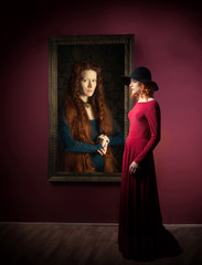 Woman standing in front of the antique female portrait hanging on a wall